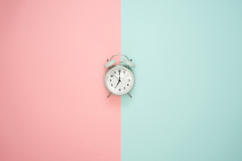 Alarm clock in front of half pink, half blue background