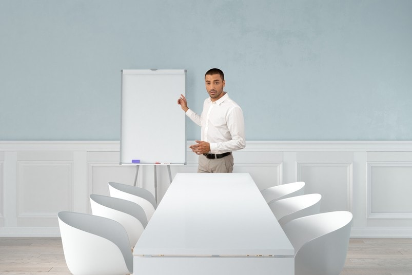 A gentleman in a white shirt pointing at a blank flipchart in an otherwise empty meeting room.