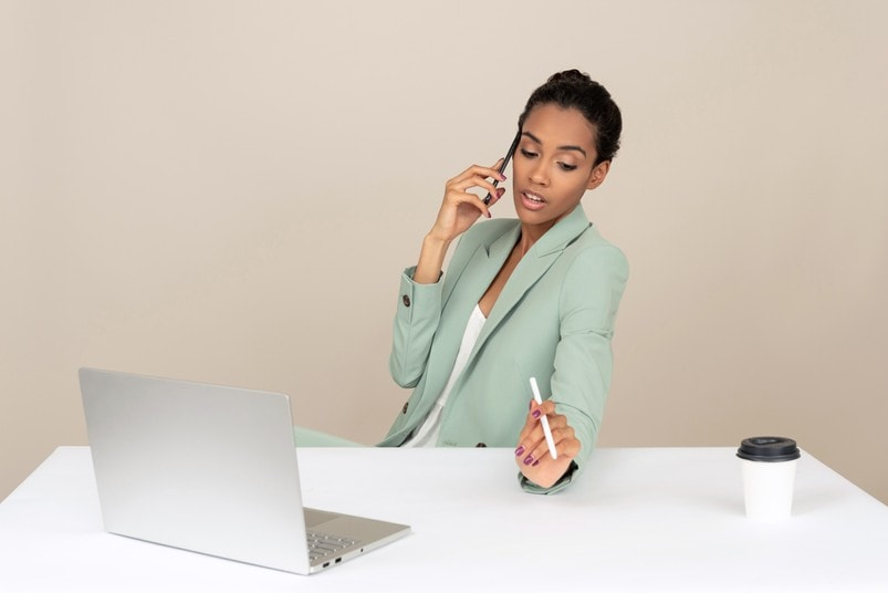 Professional woman at desk behind laptop talking on phone and holding pen