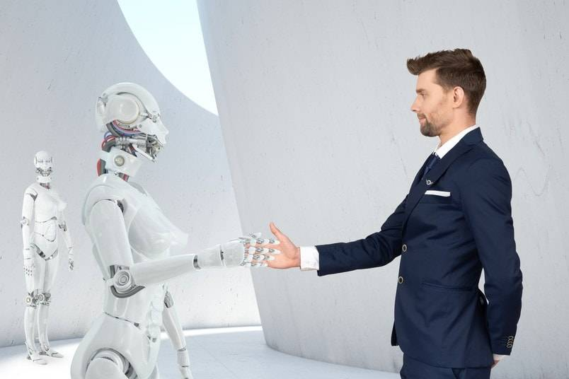 Well dressed professional man shaking hands with a futuristic-looking robot